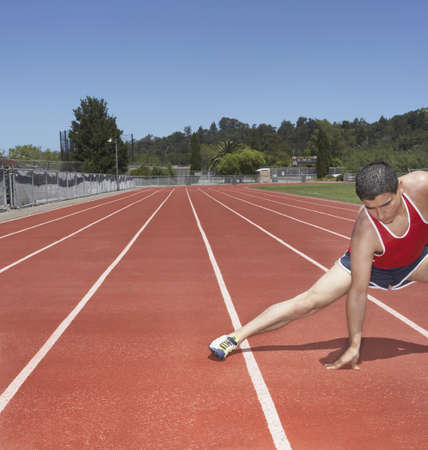 stretching condition: Male track athlete stretching