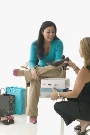 buying shoes: Vendedor de las ventas ayudando muchacha adolescente comprar zapatos