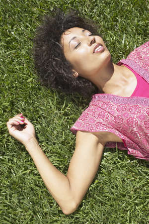 restfulness: Woman sleeping on a sunny lawn LANG_EVOIMAGES