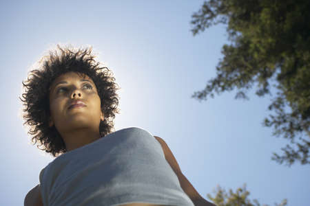 dauntless: Low angle view of woman standing against sun