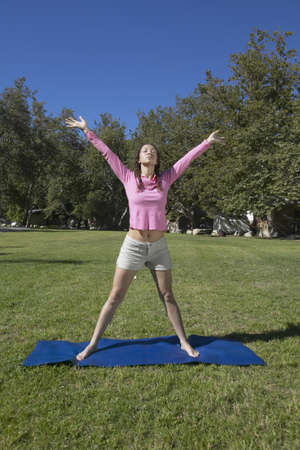 transcend: Woman practicing yoga on a mat outdoors