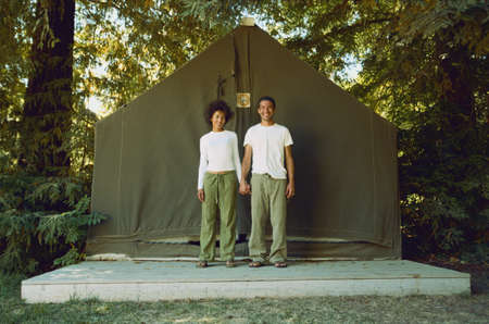 Couple standing side by side outside tent LANG_EVOIMAGES