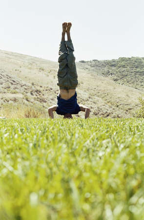 Man standing on his head in a field