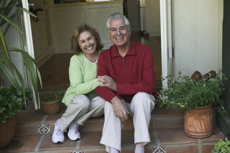 some under 18: Older hispanic couple sitting on a porch