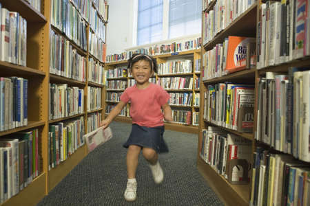aisle: Girl running down aisle of library