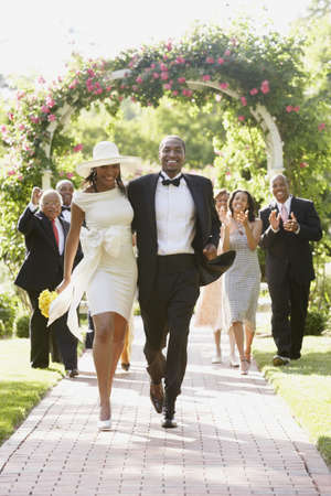 african american: Wedding guests applauding newlyweds LANG_EVOIMAGES