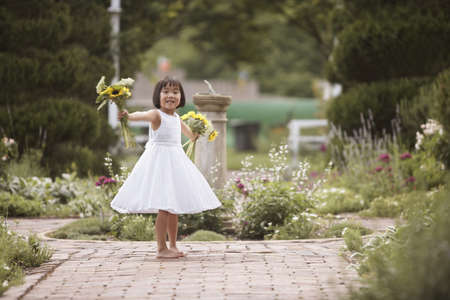 all under 18: Girl spinning while holding flowers