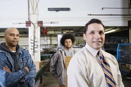 men standing: Three men standing together in warehouse