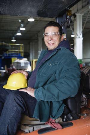 lean machine: Man in warehouse holding hardhat