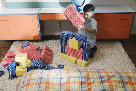chinese american ethnicity: Boy playing with cardboard blocks