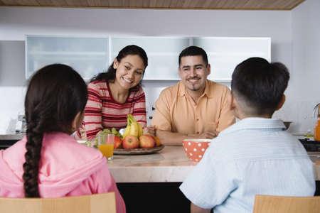 some under 18: Family gathered around kitchen counter