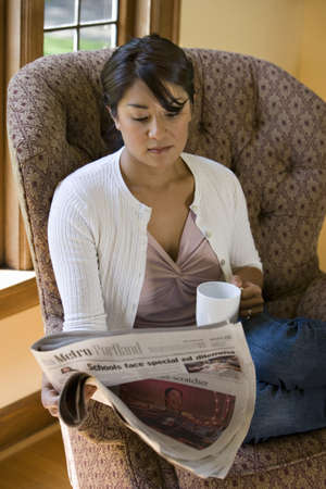 some under 18: Woman reading newspaper in chair