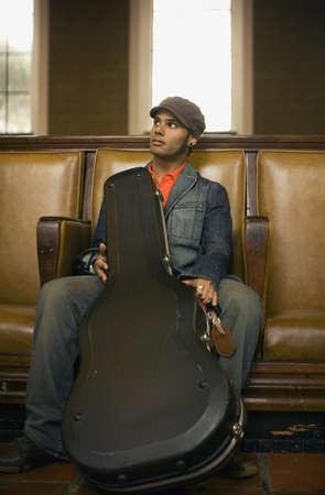 guitar case: Hombre sentado con funda de la guitarra LANG_EVOIMAGES