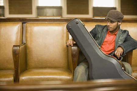 guitar case: Man sitting with guitar case