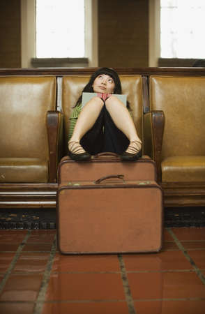 waiting glance: Woman sitting with luggage and book