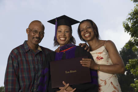 Female graduate with parents Stock Photo