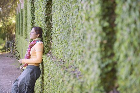 leaning by barrier: Woman leaning against a hedge LANG_EVOIMAGES