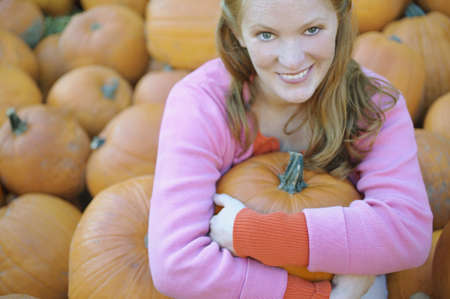 above 21: Young woman holding a pumpkin