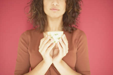 above 21: Young woman holding a cup