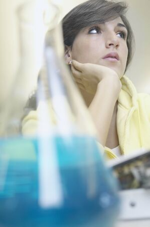 Teenage girl sitting in a laboratory thinking