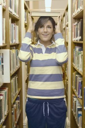 Teenage girl balancing a book on her head