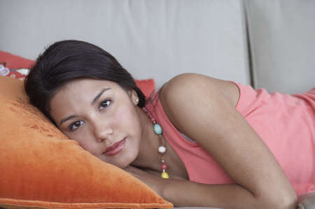woman lying down: Young woman lying down on couch
