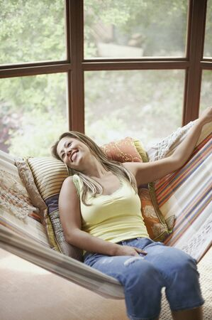 above 18: Young woman reclining on swing LANG_EVOIMAGES