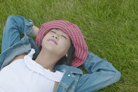 storage bin: Teenage girl lying down on a lawn