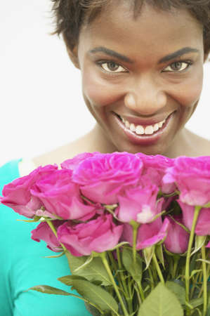 above 25: Young woman standing holding a bouquet of roses smiling