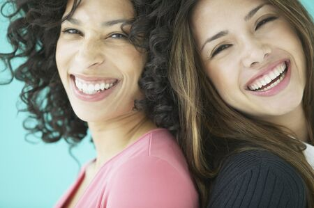 unknown age: Portrait of two young women standing back to back smiling LANG_EVOIMAGES