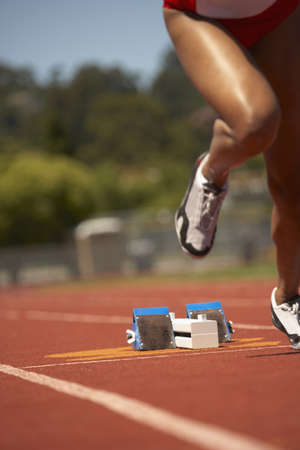 suffocation: Female runner leaving starting blocks