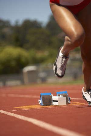 traumatized: Female runner leaving starting blocks