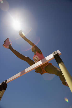 participant: Female track participant jumping over hurdle LANG_EVOIMAGES
