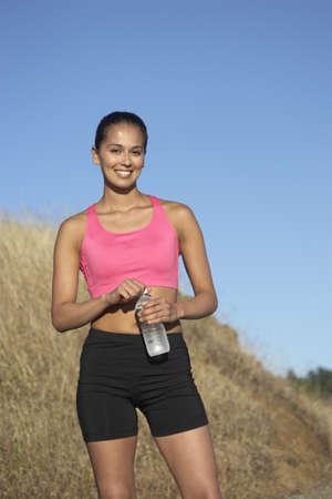 self assured: Female athlete posing on grassy hill LANG_EVOIMAGES