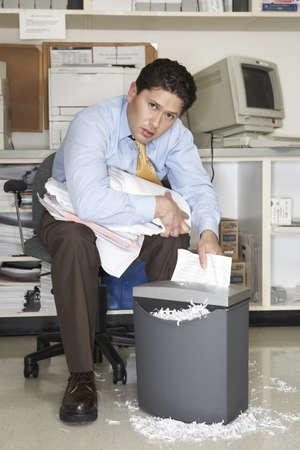 apathetic: Overworked businessman shredding documents