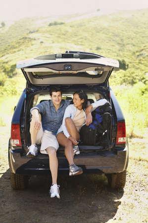 contentedness: Couple posing inside SUV hatch