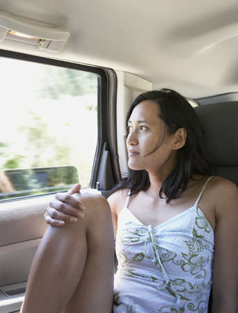 contentedness: Female passenger gazing out of car window