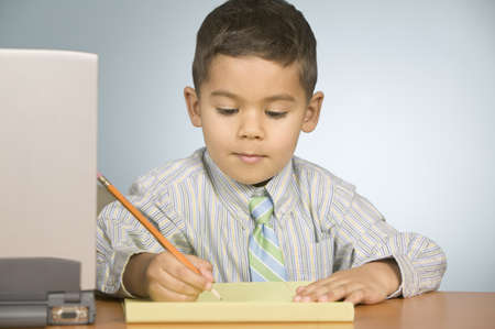 disrespect: Boy writing on notepad with a pencil