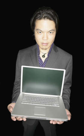 above 30: Portrait of a businessman holding a laptop