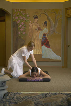 hair treatment: Young woman getting a massage by a massage therapist LANG_EVOIMAGES