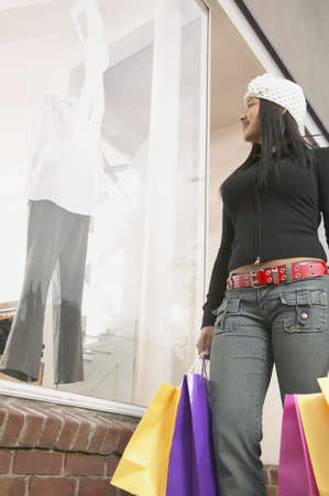 above 21: Low angle view of a young woman holding shopping bags LANG_EVOIMAGES