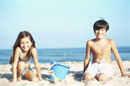 hermanos jugando: Hermano y hermana de jugar en la arena en la playa