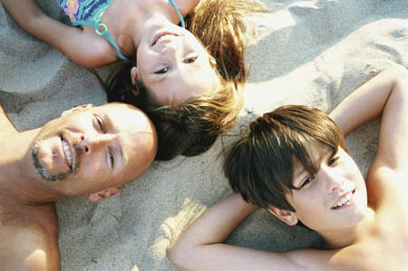 self discovery: Portrait of a family lying on beach sand LANG_EVOIMAGES