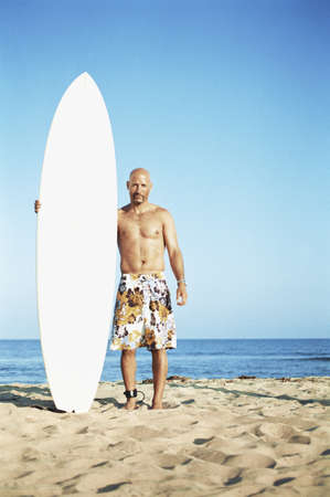 some under 18: Man posing beside his surfboard