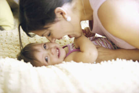 above 21: Mother playing with toddler on bed