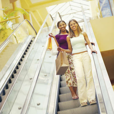 descend: Girlfriends descend escalator in shopping mall LANG_EVOIMAGES