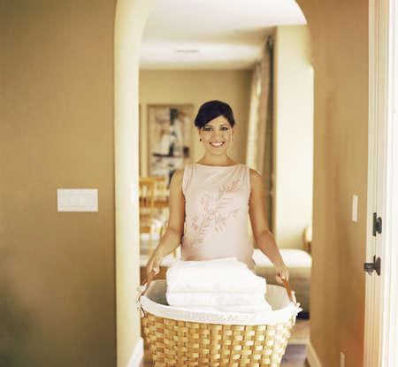 one sheet: Teen girl holding basket of folded laundry LANG_EVOIMAGES