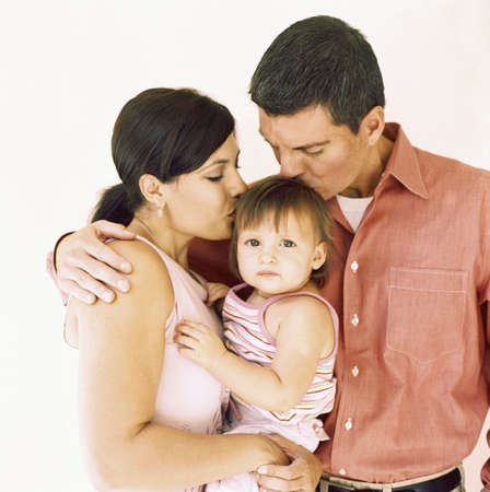 above 21: Couple kissing their baby girl