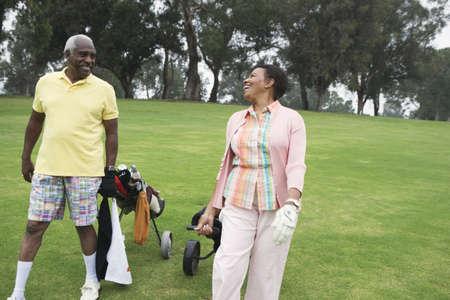 sidewalk talk: Golfing couple enjoying a laugh