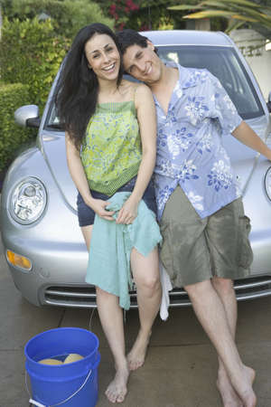 washing car: Young couple washing car together